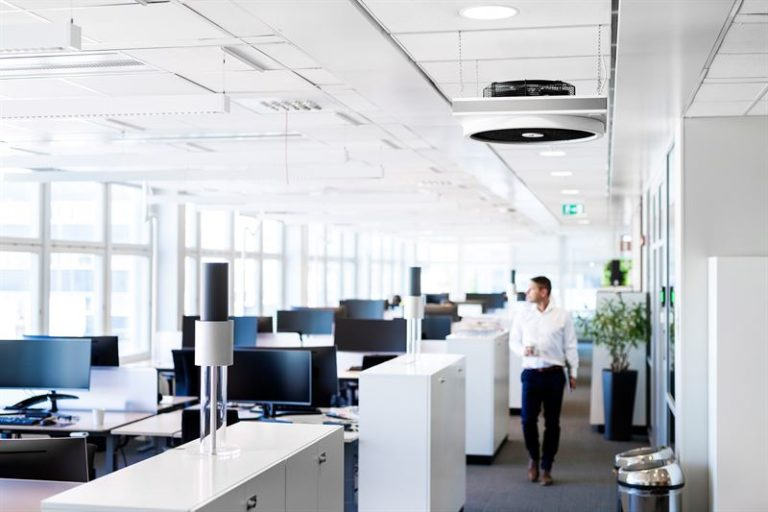 Man walking in large bust office with lightair ionflow air purifiers displayed