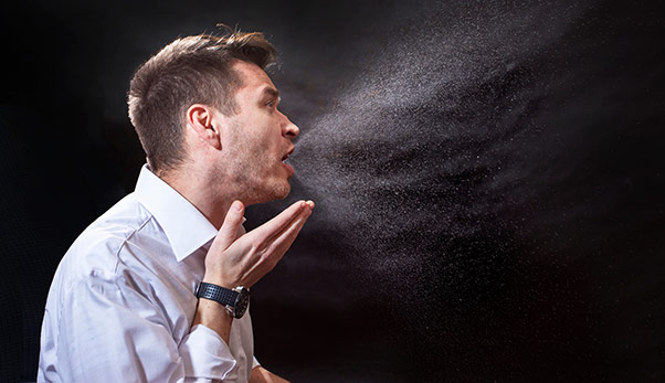 Man coughing into hand showing viral spread in droplets